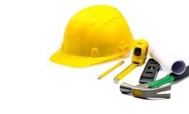 有图纸的黄色安全帽和铅笔,卷尺,锤子,建筑在白色背景隔绝的气泡水准,拷贝空间, 免版税库存照片