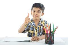 有图画笔记和铅笔的印地安男孩 库存图片