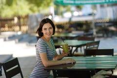 有圆滑的人的正面女孩 坐在被弄脏的咖啡馆背景的微笑的妇女 户外咖啡馆概念 复制空间 库存图片