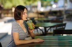 有圆滑的人的正面女孩 坐在被弄脏的咖啡馆背景的微笑的妇女 户外咖啡馆概念 复制空间 免版税库存图片