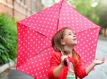 有圆点伞的小女孩在雨下 免版税库存图片