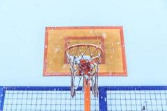 有圆环和栅格的篮球盾反对天空在冬天 免版税库存照片