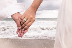 有圆环的手在海滩 库存照片