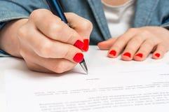 有圆珠笔签署的合同文件的妇女 图库摄影