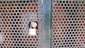 有圆的保险开关孔的被挂锁的金属碗柜 免版税库存照片