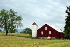 有圆的干草捆的红色谷仓 库存照片