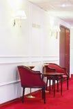 有圆的木桌的两把红色扶手椅子在隆重 免版税库存照片