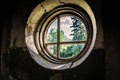 有圆的窗口的被破坏的老室 库存照片