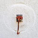 有圆的踪影的生锈的门锁环在白色墙壁上 免版税库存照片