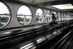 有圆窗口的机场移动的走道在黑白 免版税库存照片