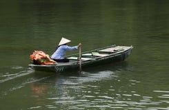 有圆锥形帽子的越南妇女用浆划她的小船的 库存照片