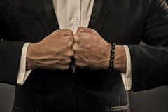 有圆鼓的静脉和镯子的男性拳头在正装背景 交锋概念 企业人的手 免版税库存照片