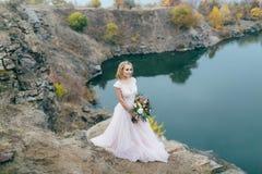 有土气花束的时髦的新娘在小山的一个湖前摆在 秋天户外婚礼 全长 免版税库存图片