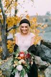 有土气花束的时髦的新娘在小山的一个湖前摆在 一个被编织的帽子的年轻金发碧眼的女人有大型机关炮的和 免版税库存图片