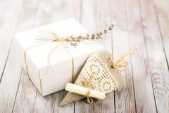 有土气麻线的白色礼物盒和淡紫色,手工制造心脏小树枝  库存照片