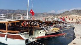 有土耳其旗子的许多游艇在山背景在爱琴海 库存照片