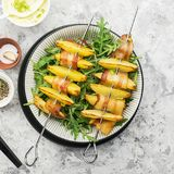 有土豆切片的开胃串在烤箱烘烤的烟肉切片服务用酸奶和一道蔬菜沙拉 顶视图 库存图片