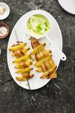 有土豆切片的开胃串在烤箱烘烤的烟肉切片服务用酸奶和一道蔬菜沙拉 顶视图 免版税图库摄影