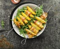 有土豆切片的开胃串在烤箱烘烤的烟肉切片服务用酸奶和一道蔬菜沙拉 顶视图 免版税库存图片
