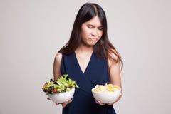 有土豆片和沙拉的年轻亚裔妇女 免版税库存图片