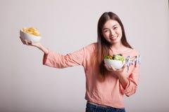 有土豆片和沙拉的年轻亚裔妇女 免版税库存照片