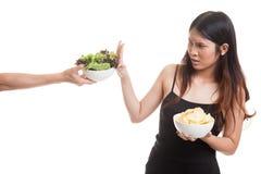 有土豆片的年轻亚裔妇女对沙拉说不 图库摄影