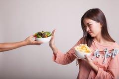 有土豆片的年轻亚裔妇女对沙拉说不 免版税库存照片