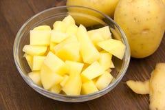 有土豆立方体的碗在木头 免版税库存照片