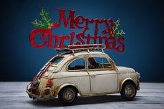 有圣诞快乐标志的减速火箭的玩具汽车 免版税库存图片