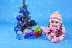 有圣诞树和礼品的小女孩 免版税库存照片