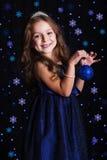 有圣诞树玩具的愉快的女孩在光 免版税库存图片
