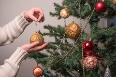 有圣诞树球装饰的手 库存照片
