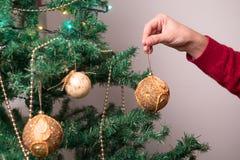 有圣诞树球装饰的手 免版税库存照片