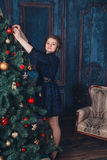有圣诞树的女孩 免版税库存图片
