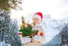 有圣诞树的妇女和在山前面的礼物盒  免版税库存照片