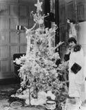 有圣诞树的妇女和礼物(所有人被描述不更长生存,并且庄园不存在 供应商保单Th 免版税图库摄影