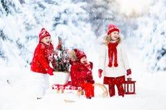 有圣诞树的孩子 雪孩子的冬天乐趣 免版税库存照片