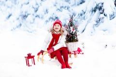 有圣诞树的孩子 雪孩子的冬天乐趣 库存图片