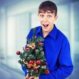有圣诞树的少年 免版税库存图片