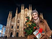 有圣诞树的微笑的妇女和礼物在米兰,意大利 库存图片