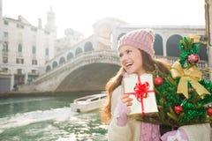 有圣诞树的愉快的妇女和礼物盒在威尼斯,意大利 免版税库存图片