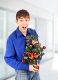 有圣诞树的愉快的少年 免版税库存图片