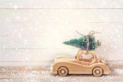 有圣诞树的木玩具汽车在一张木桌上的屋顶 库存图片