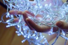 有圣诞灯的手 免版税库存照片