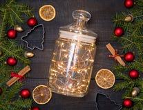 有圣诞灯的玻璃瓶子在黑暗的木土气背景 免版税图库摄影