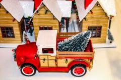 有圣诞灯的葡萄酒红色玩具卡车和树在国家圣诞节村庄前面支持 库存图片