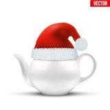 有圣诞老人圣诞节帽子的陶瓷茶壶  库存照片