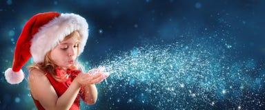 有圣诞老人帽子吹的雪的小女孩 库存照片