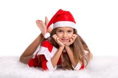 有圣诞老人帽子和衣服的逗人喜爱的微笑的女孩 免版税库存照片