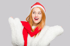 有圣诞老人帽子微笑的看的美丽的少妇对惊奇的边 免版税库存图片